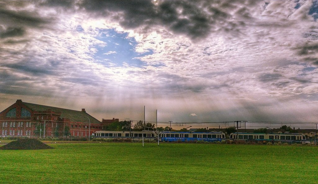 An image of clouds over a school field with the sun rays shining through